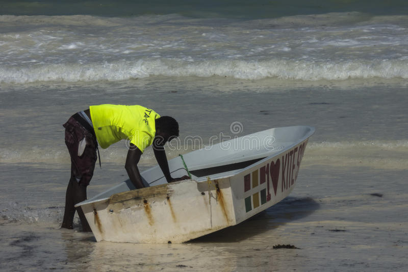 People on Zanzibar beach. Man cleaning boat on tropical beach in Kiwengwa Village on Zanzibar Island. Tanzania , Africa stock photos