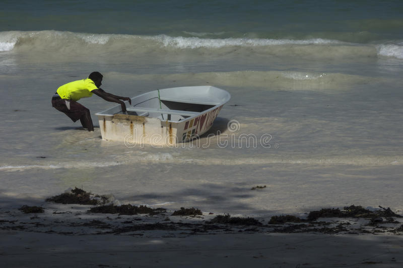 People on Zanzibar beach. Man cleaning boat on tropical beach in Kiwengwa Village on Zanzibar Island. Tanzania , Africa royalty free stock photography