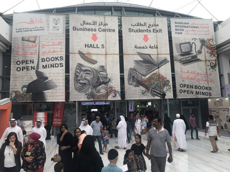 Peoples walking under display signage at Sharjah International Book Fair royalty free stock photo