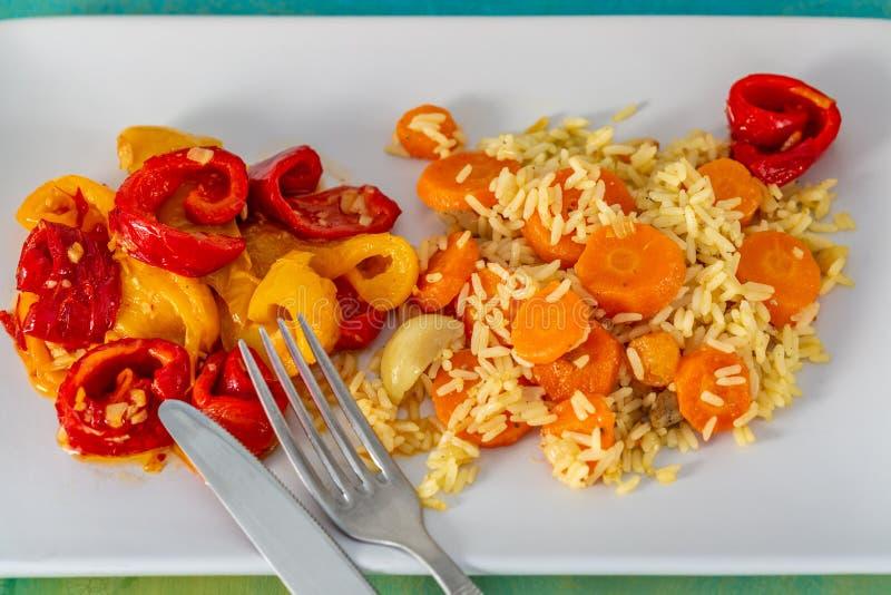 Pepe giallo rosso al forno e riso bianco cucinato con le carote deliziose su un piatto e una forcella e un coltello ceramici bian fotografia stock libera da diritti