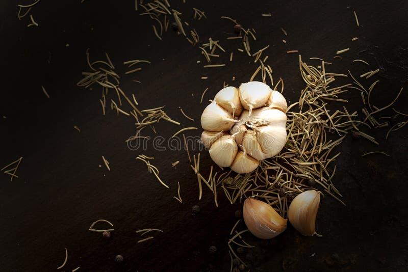 Pepe nero, aglio e rosmarini sul piatto di legno su backg nero fotografia stock libera da diritti
