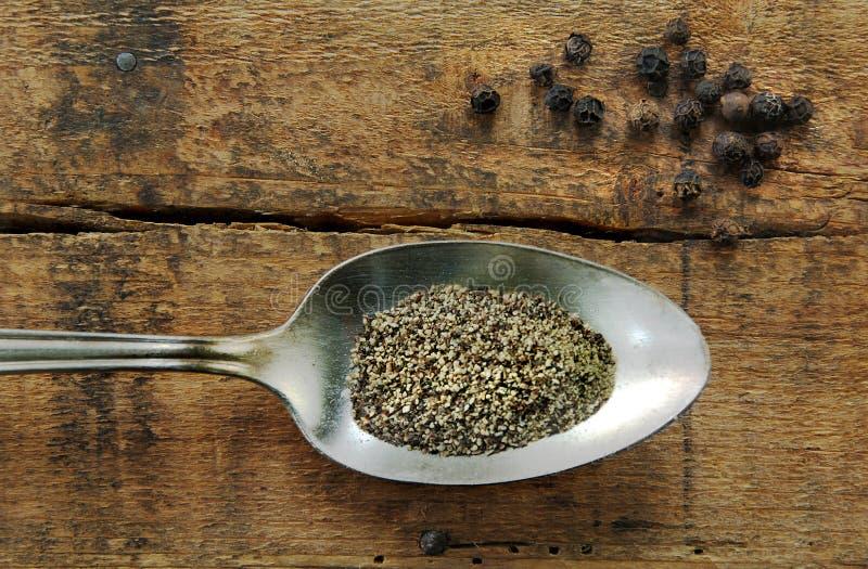 Pepe nero e granelli di pepe a terra fotografie stock