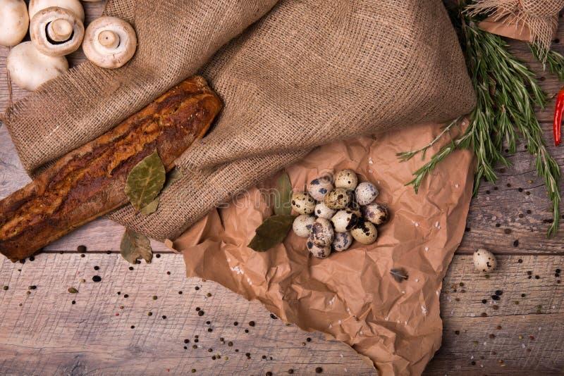 Pepe nero, funghi e rosmarini su un fondo della tavola Uova crostose di quaglia e del pane Vista superiore degli ingredienti rust immagini stock