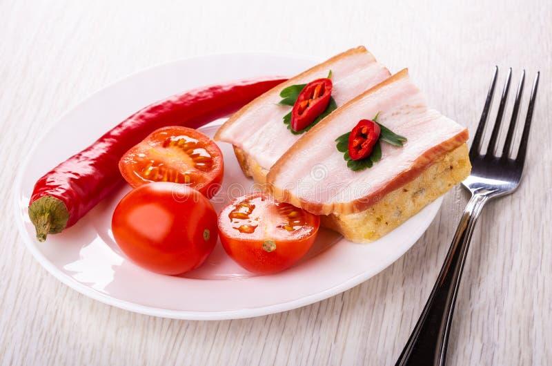 Pepe, pomodori, panino con il petto in piatto, forcella sulla tavola fotografia stock