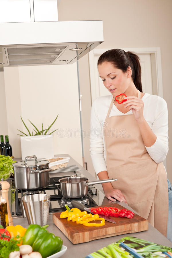 Pepe rosso mordace della donna felice in cucina moderna immagini stock
