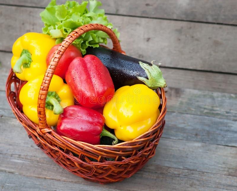 Peper met tomaten, sla en aubergine in mand op houten achtergrond stock afbeelding