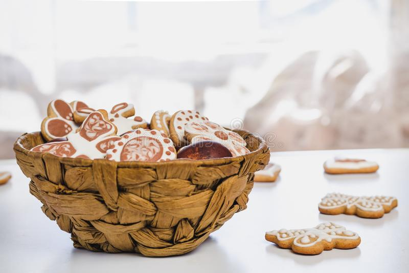 Peperkoek, met wit en chocolade suikerglazuur-suiker wordt behandeld, en Pasen-kippeneieren in een bruine rieten mand die royalty-vrije stock fotografie