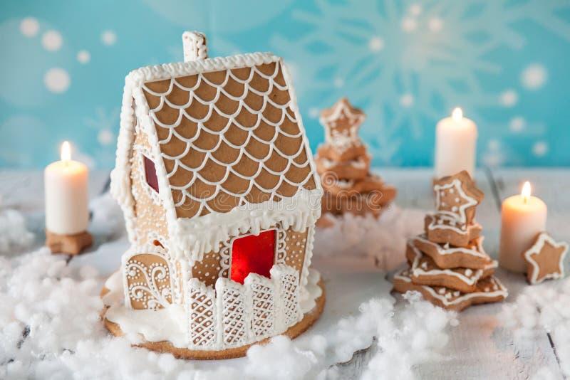 Peperkoekhuis en peperkoekbomen op een feestelijke Kerstmisachtergrond stock afbeelding