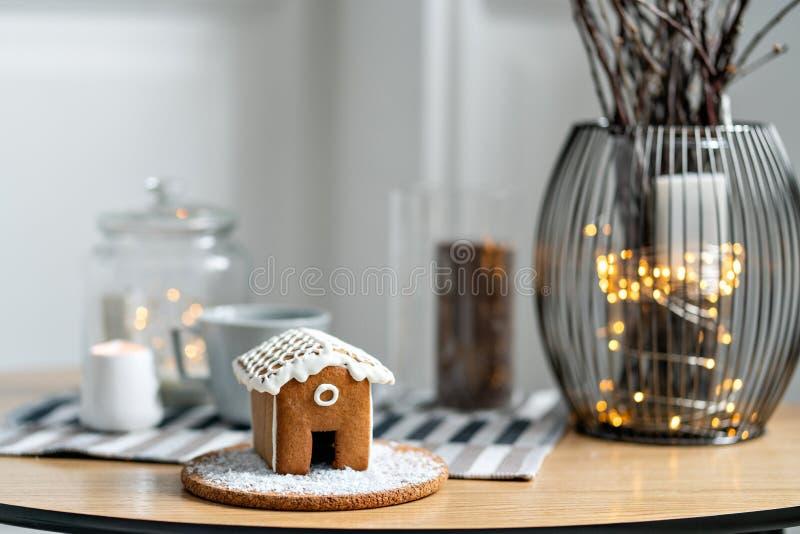 Peperkoekhuis op houten lijst De lichten van de Defocusedslinger op achtergrond Kerstboom en Vakantiestemming Ochtend binnen royalty-vrije stock afbeeldingen