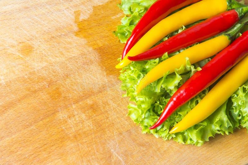 Peperoncini caldi sulle foglie della lattuga su fondo di legno Copi lo spazio immagini stock