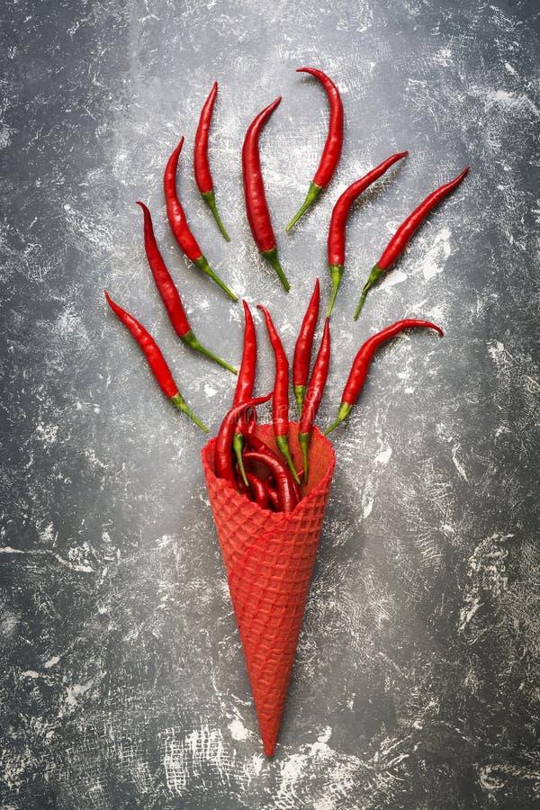 Peperoncini nel cono rosso della cialda su un fondo rustico grigio Il concetto di cibo e di peperoncini Vista superiore, spazio p fotografie stock