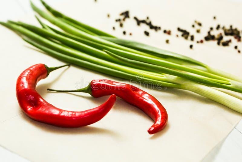 Peperoncini rossi freschi e cipolle verdi su un fondo bianco immagini stock