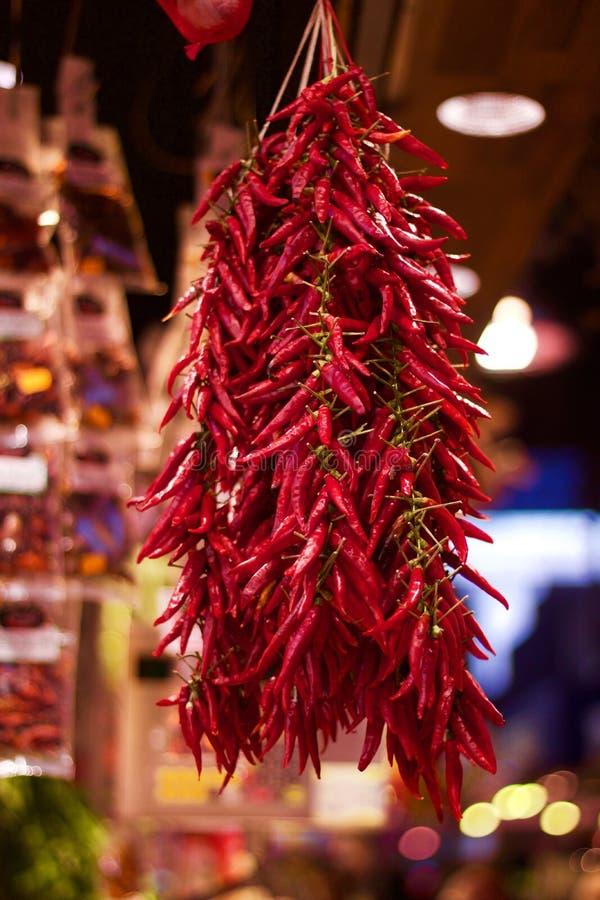 Peperoncini rossi rossi secchi che appendono in vendita nel mercato immagine stock