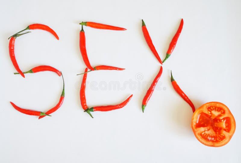 Peperoncini roventi e bugia mezza del pomodoro su una superficie bianca Le verdure compongono il sesso di parola Condimento e sal fotografia stock