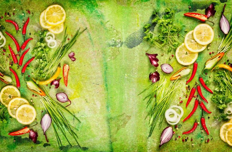 Peperoncino rosso fresco, cipolla, limone ed erbe aromatiche vari per la cottura sul fondo rustico verde immagini stock