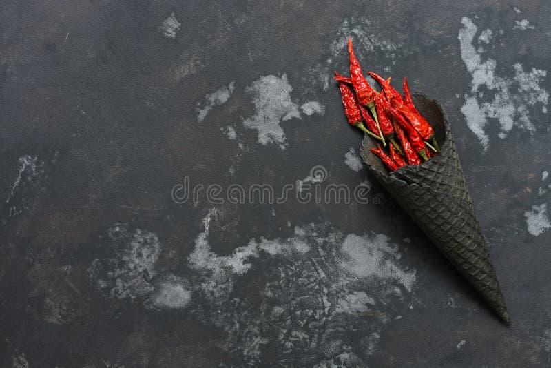Peperoncino rosso secco in un corno nero della cialda Fuoco dal peperoncino rosso, l'immagine di una torcia Vista sopraelevata e  fotografia stock libera da diritti
