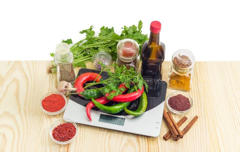 Peperoncino rosso sulla scala della cucina e varie spezie, erbe e salsa fotografia stock libera da diritti