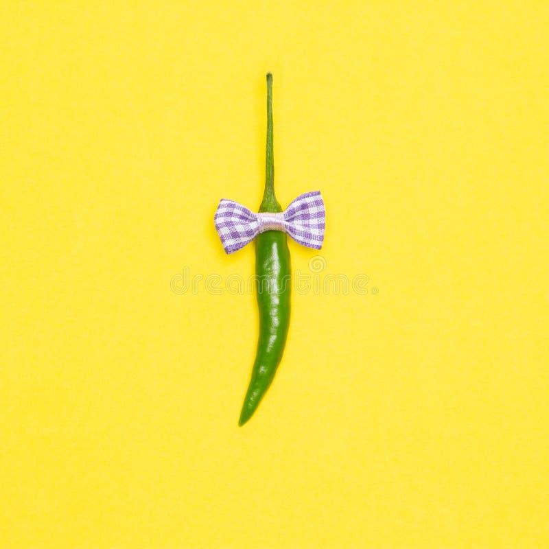 Peperoncino verde con la cravatta a farfalla su fondo giallo Concetto minimalistic allegro immagini stock