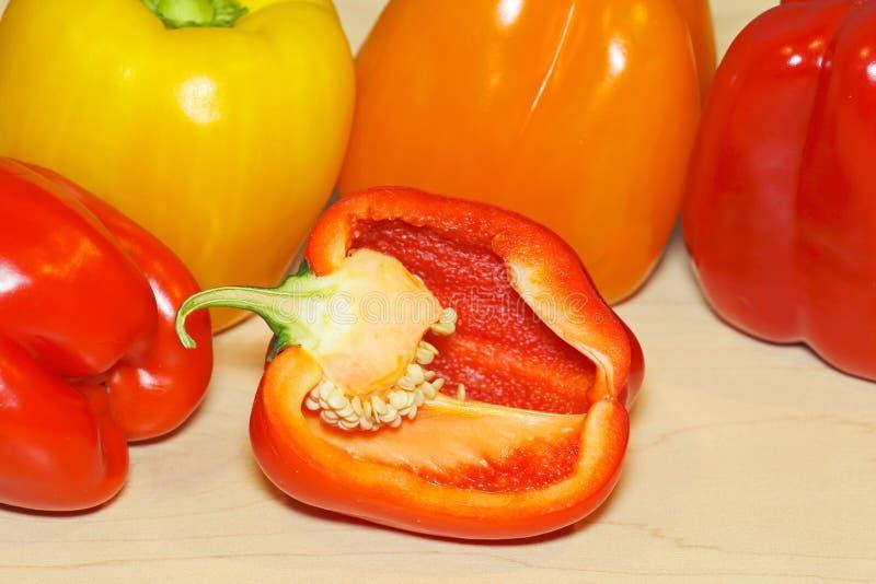 Peperone dolce rosso affettato a metà con varia paprica colorata nel fondo sul bordo dell'acero fotografie stock