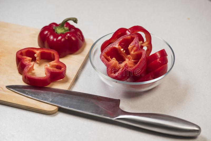 Peperone dolce rosso fresco su un bordo di legno ed in una ciotola di vetro, vicino al coltello fotografie stock libere da diritti