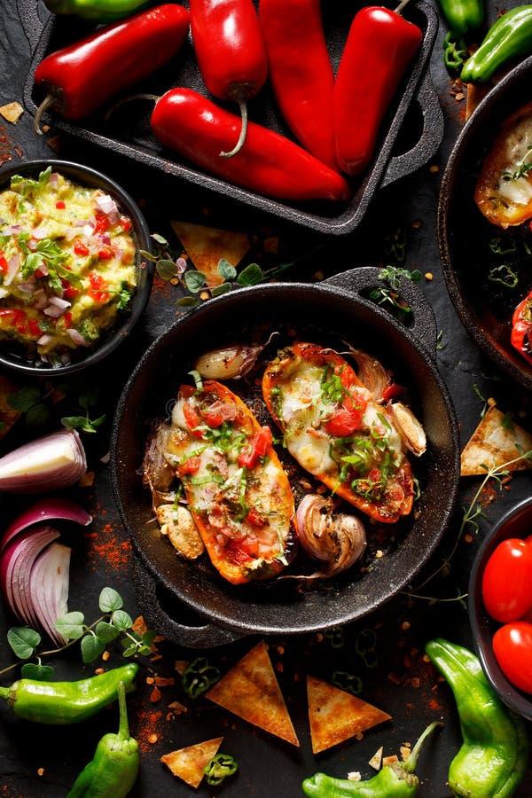 Peperoni arrostiti farciti con formaggio, bacon, le verdure e le erbe, miscela degli aperitivi deliziosi su un fondo nero immagini stock libere da diritti