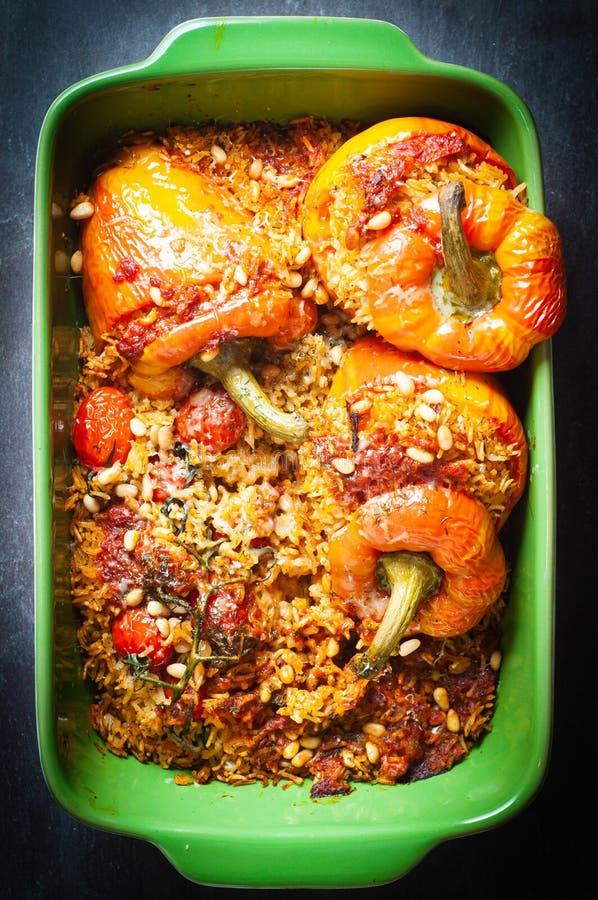 Peperoni a campana di fiamma ripieni di riso aromatico speziato e cotto nel forno immagine stock