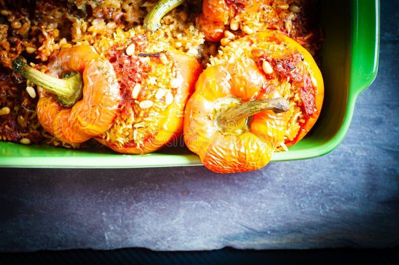 Peperoni a campana di fiamma ripieni di riso aromatico speziato e cotto nel forno fotografia stock libera da diritti