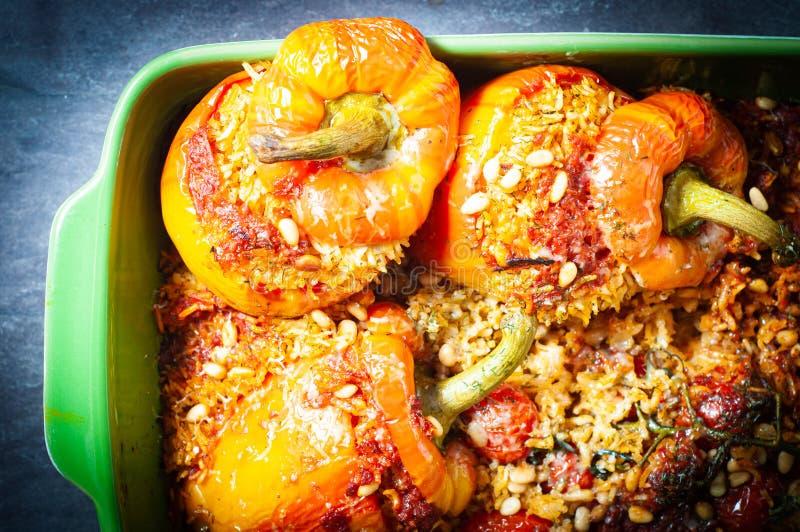 Peperoni a campana di fiamma ripieni di riso aromatico speziato e cotto nel forno fotografia stock