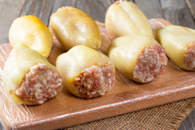 Peperoni crudi farciti con carne e riso su un tagliere immagine stock