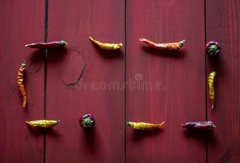 Peperoni del Cile su fondo di legno rosso Vista superiore immagine stock