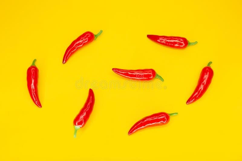 Peperoni di peperoncini rossi rossi su priorit? bassa gialla Ingrediente di cucina messicana Disposizione piana immagini stock libere da diritti