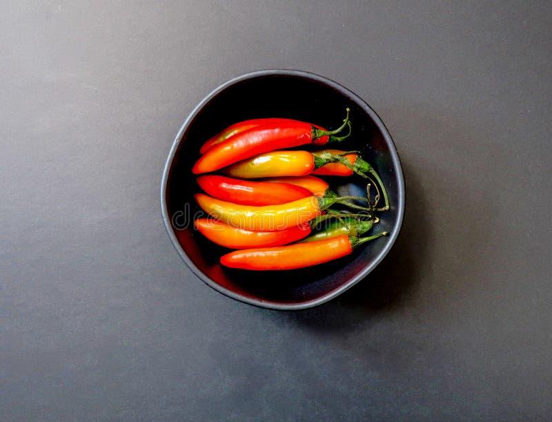 Peperoni di peperoncino rosso rosso freschi in un piatto nero, fondo nero immagini stock libere da diritti