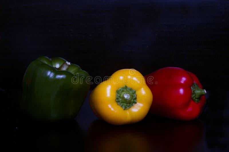 Peperoni dolci dei colori differenti su fondo nero immagine stock