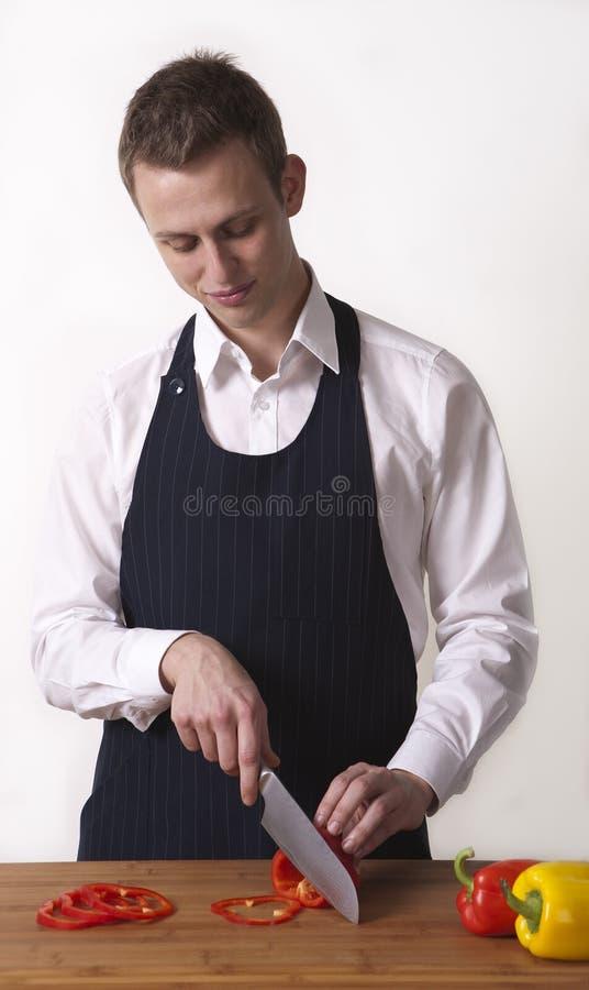 Peperoni dolci di giovane taglio del cuoco unico. fotografia stock