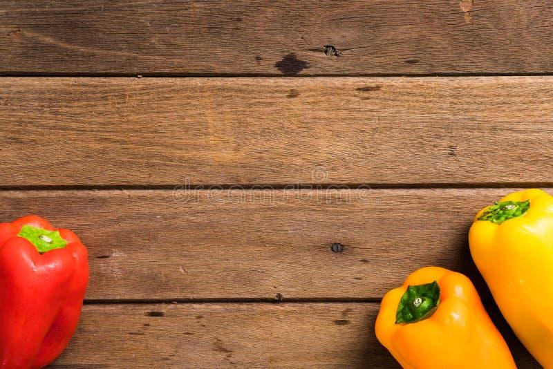 Peperoni dolci rossi della verdura fresca/arancio organici su backgr di legno fotografie stock