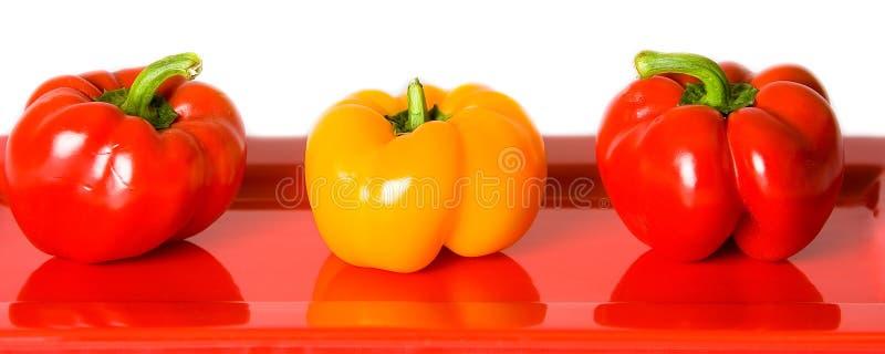 Peperoni dolci rossi e gialli su una zolla rossa. fotografia stock libera da diritti