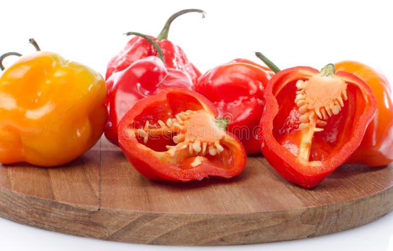 Peperoni freschi del habanero sul tagliere fotografie stock