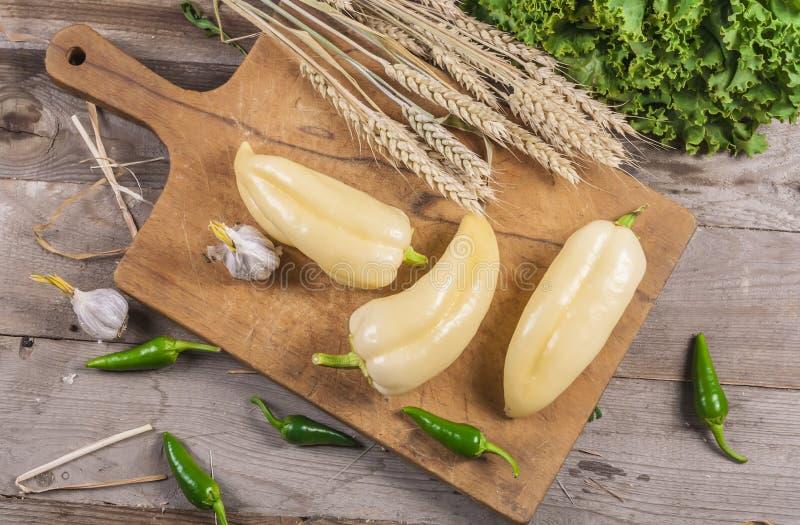 Peperoni freschi sul supporto di legno Alimenti vegetariani fotografia stock libera da diritti