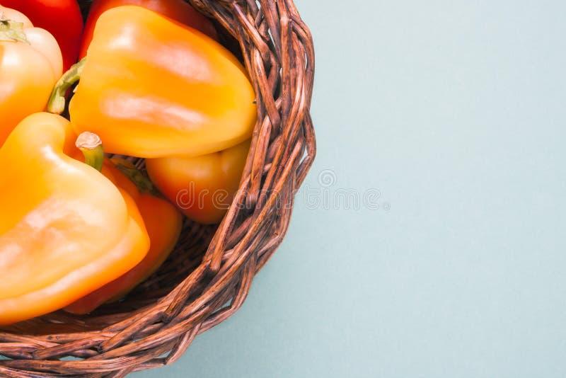 Peperoni gialli arancio maturi delle verdure in un canestro su fondo blu con lo spazio della copia immagini stock libere da diritti