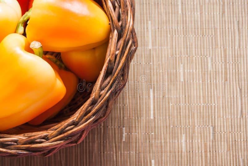Peperoni gialli arancio maturi delle verdure in un canestro su fondo rustico beige con lo spazio della copia fotografia stock