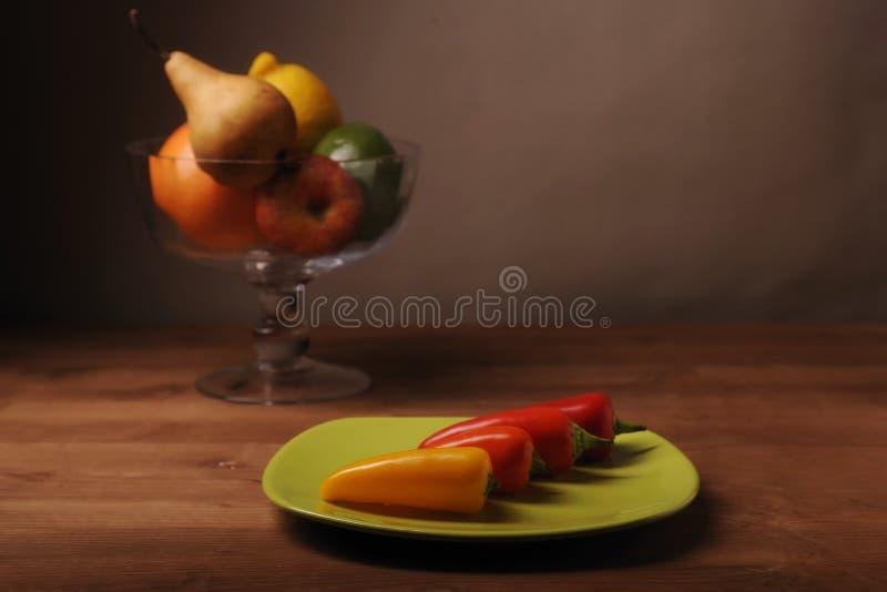 Peperoni nel piatto verde fotografia stock