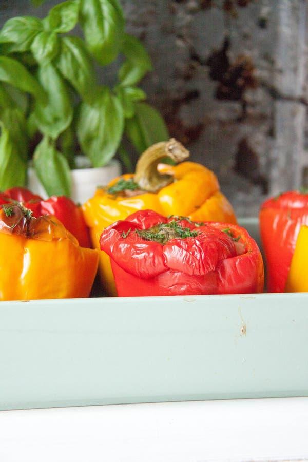 Peperoni rossi e gialli farciti con carne, il pomodoro ed il formaggio in un piatto di cottura immagini stock