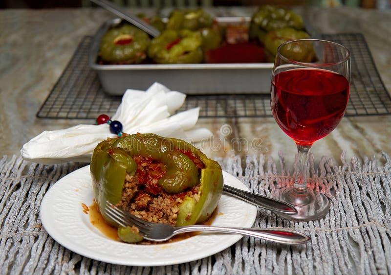 Peperoni verdi farciti in salsa al pomodoro con vetro di vino rosso Fondo bollente del piatto immagini stock libere da diritti