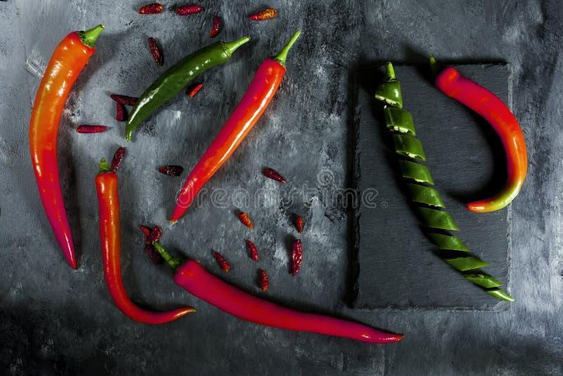 Peperoni verdi, freschi e piccanti, affettati su ardesia, di Caienna e peperoni rossi freschi immagine stock