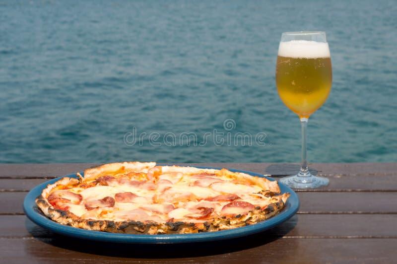 Peperonipizza och exponeringsglas av öl på trä och vattenbakgrund fotografering för bildbyråer