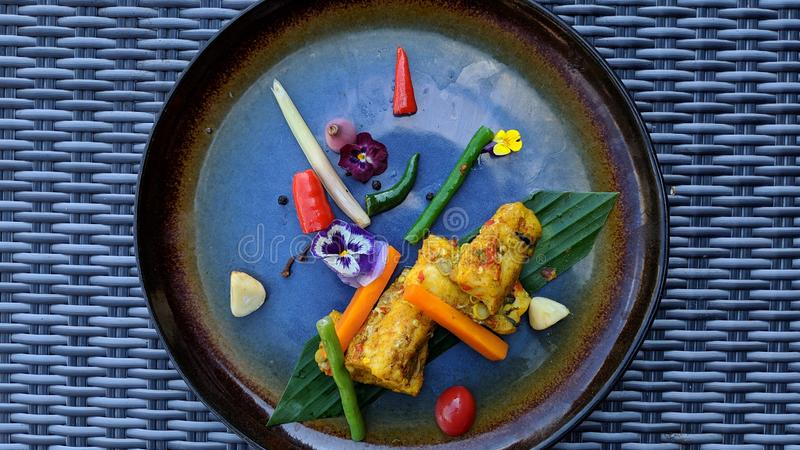 Pepes Ikan is an Indonesian cooking method using banana leaf as food wrappings served on fancy plate. Delicious food stock photography