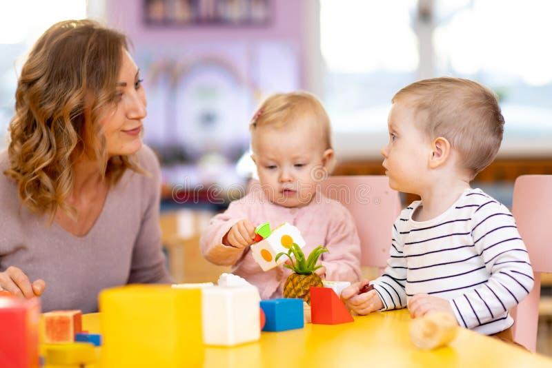Pepinier dzieci bawić się zabawki z nauczycielem w playroom przy preschool jest edukacja starego odizolowane pojęcia zdjęcia stock