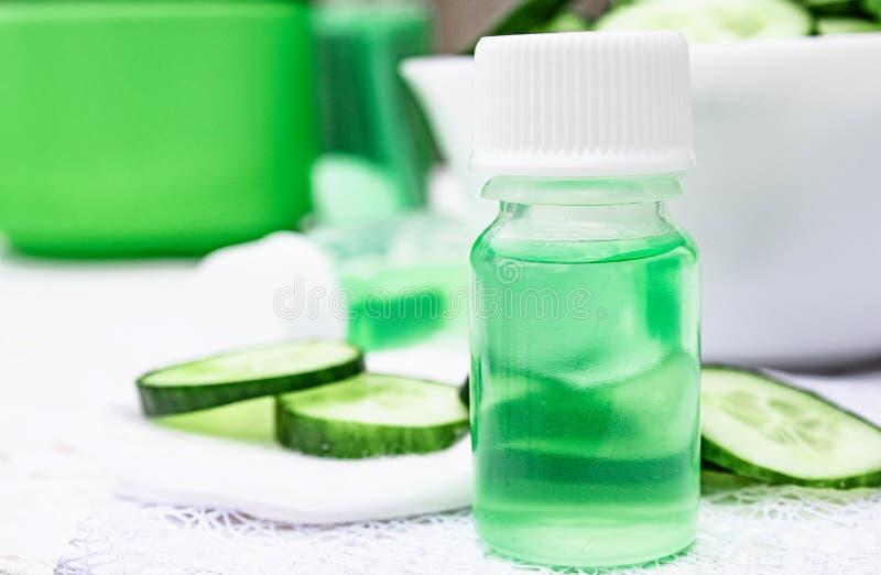 Pepino cortado y una botella de extracto del pepino Cosméticos líquidos para el cuidado de piel imágenes de archivo libres de regalías