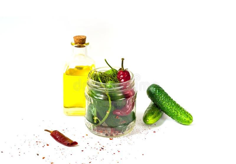Pepino no frasco de vidro, em pepinos conservados com especiarias e em azeite fotos de stock royalty free