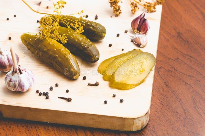 Pepinos, ajo y especias verdes conservados en vinagre en un tablero de madera foto de archivo libre de regalías